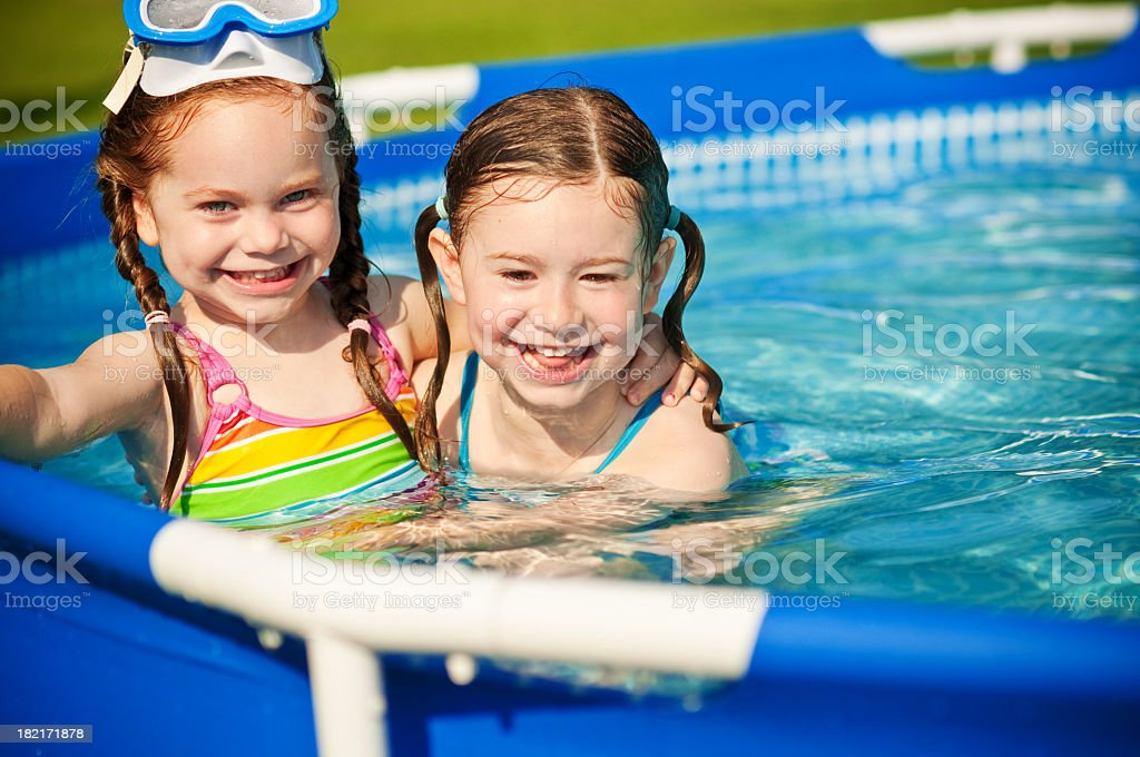 Two Happy Sisters in a Swimming Pool royalty-free stock photo