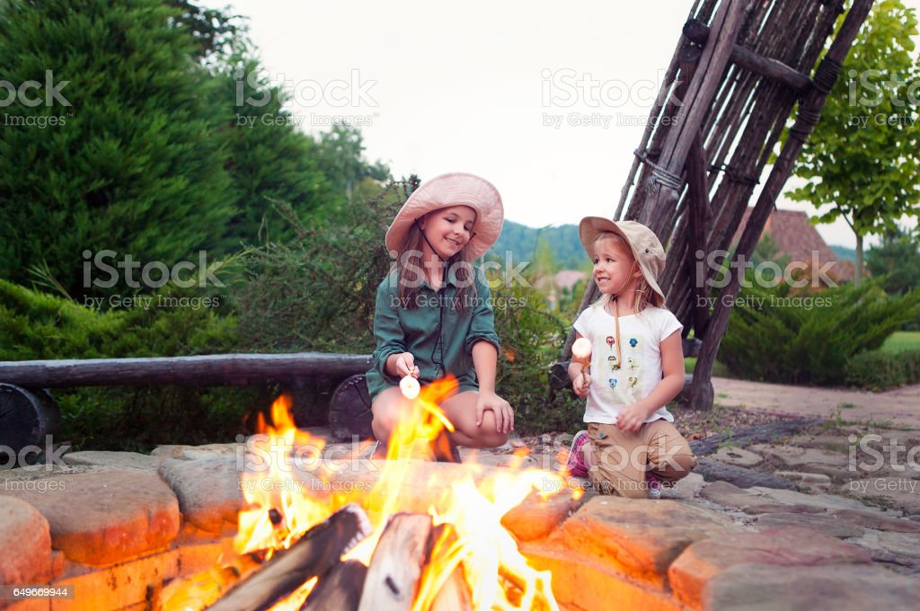 Two happy sisters roasting marshmallows stock photo