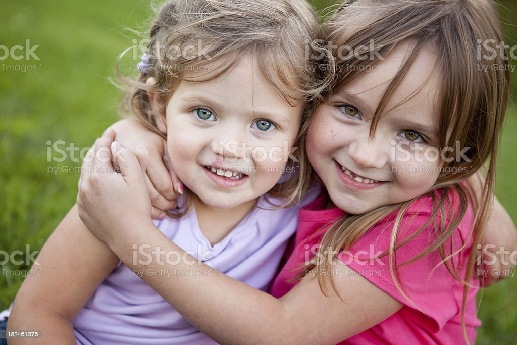 Two Happy Sisters Smiling and Hugging Outside royalty-free stock photo