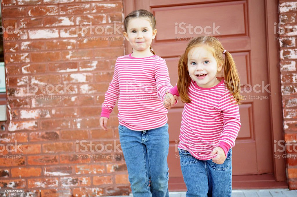 Two Happy Sisters Walking and Holding Hands royalty-free stock photo