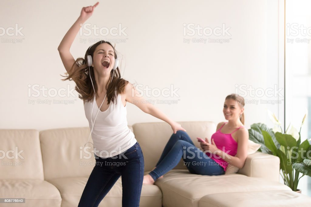 Two happy teenager girl enjoying music at home stock photo