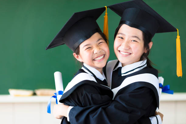 Two happy teenager in graduation gowns hugging and smiling stock photo