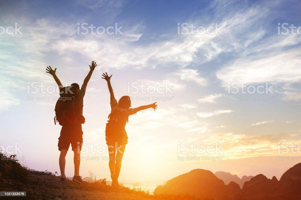 Dos turistas felices saludos salida del sol en las montañas - foto de stock