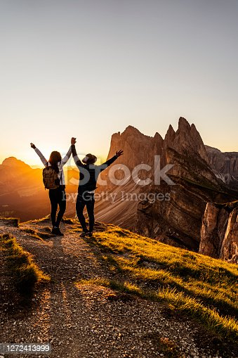Two happy tourists backpackers greetings sunrise or at mountains top of South Tirol with a great view by sunset.