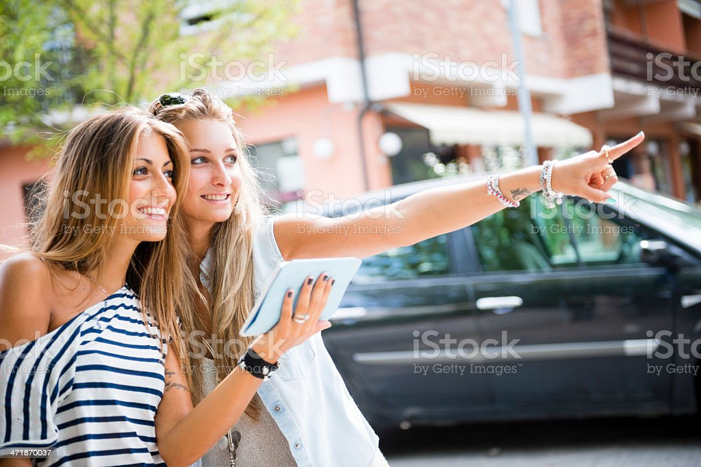Two happy woman using digital tablet royalty-free stock photo