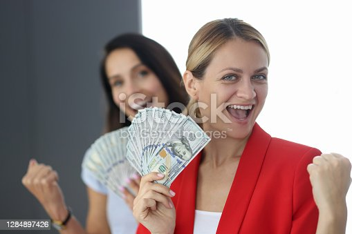 Two happy women are holding fan of one hundred dollar bills. Earning money for women at home concept