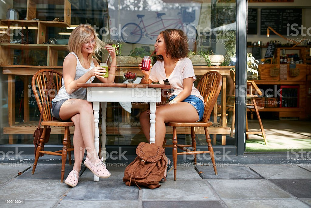 Two happy women at cafe enjoying drinks and chat stock photo