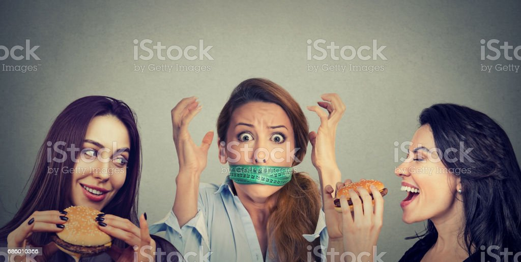 Dos mujeres felices comiendo hamburguesas mirando destacó niña con cinta alrededor de su boca de medición. - foto de stock