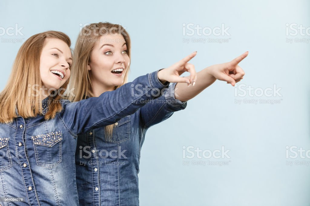 Two happy women friends wearing jeans outfit poitning - Royalty-free Adult Stock Photo
