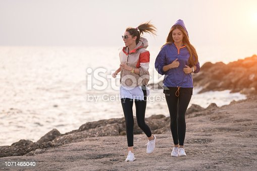 Two happy women jogging by the sea