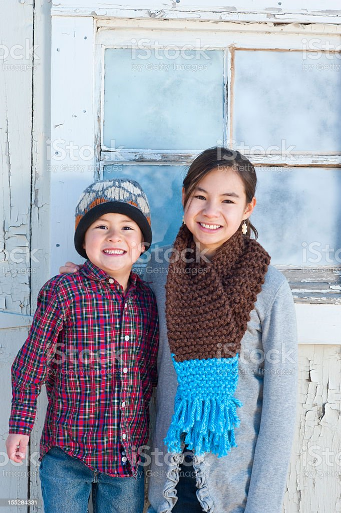 Two happy young children smiling in front of old house stock photo