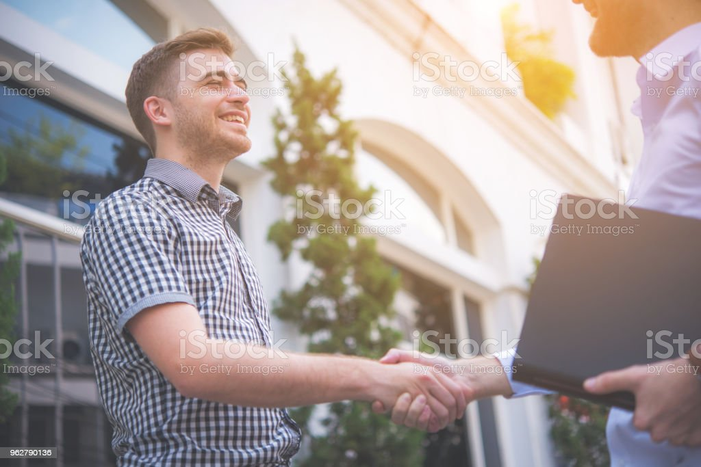 Two happy young men shaking hands with town building background - Foto stock royalty-free di Accordo d'intesa