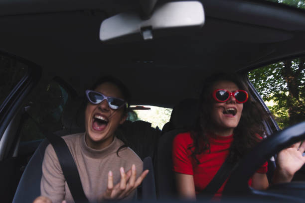 Two happy young women having fun in car Two young women traveling in car singing stock pictures, royalty-free photos & images