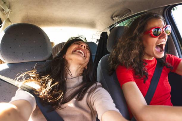 Two happy young women having fun in car stock photo