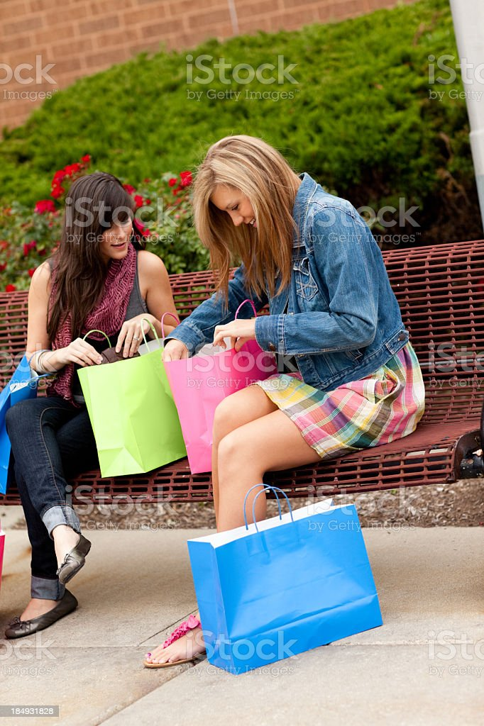 Two Happy Young Women Looking in Shopping Bags Outside Mall stock photo