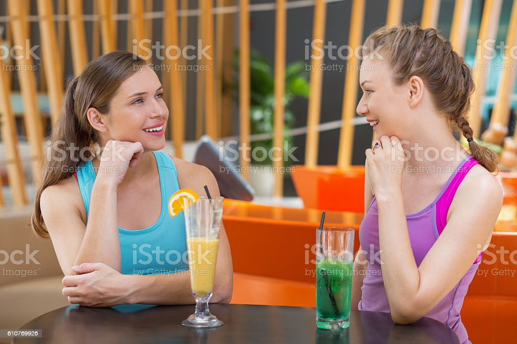 Two Happy Young Women Talking in Fitness Cafe stock photo