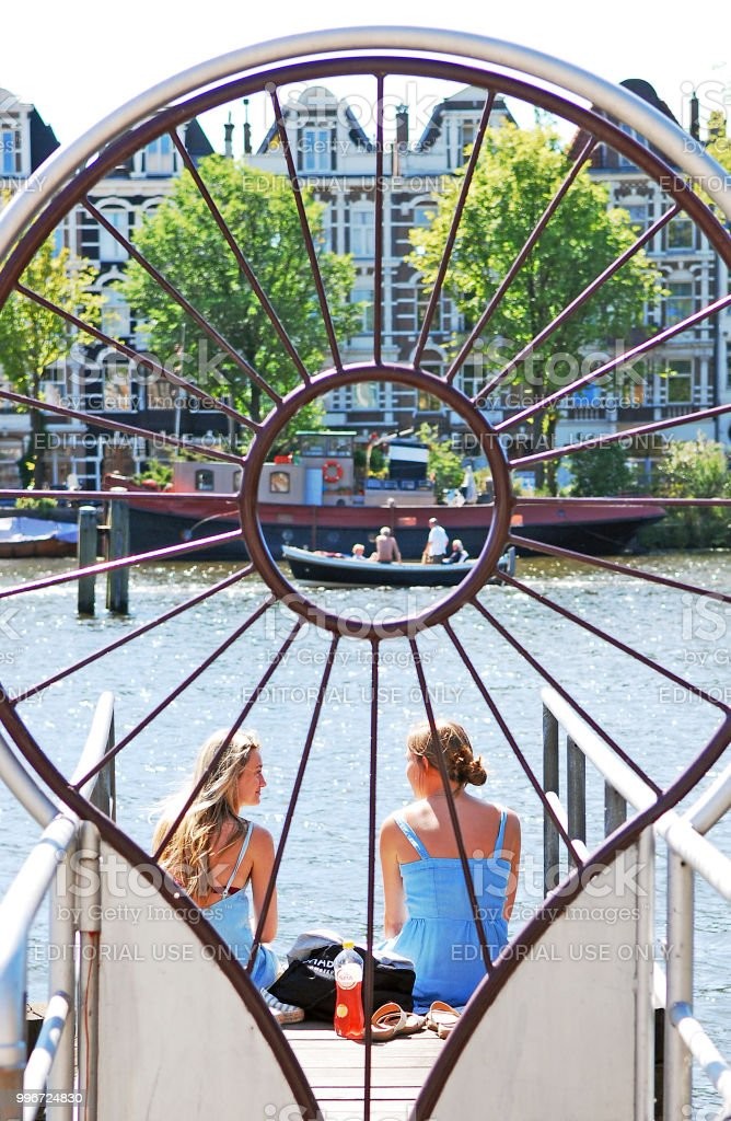 Two happy young women talking on the Amstel river pier. stock photo