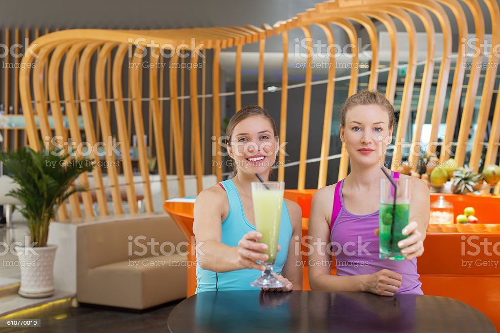 Two Happy Young Women with Smoothies in Sport Cafe stock photo