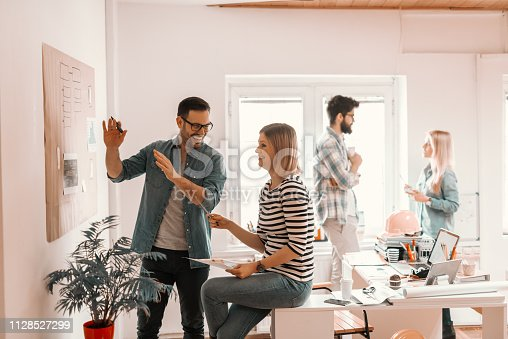 istock Two hard working young colleagues developing business plan in office. In background man and woman talking. Start up business concept. 1128527299