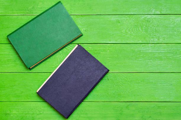 Yeşil ahşap arka planda Iki sert kapak kitabı stok fotoğrafı