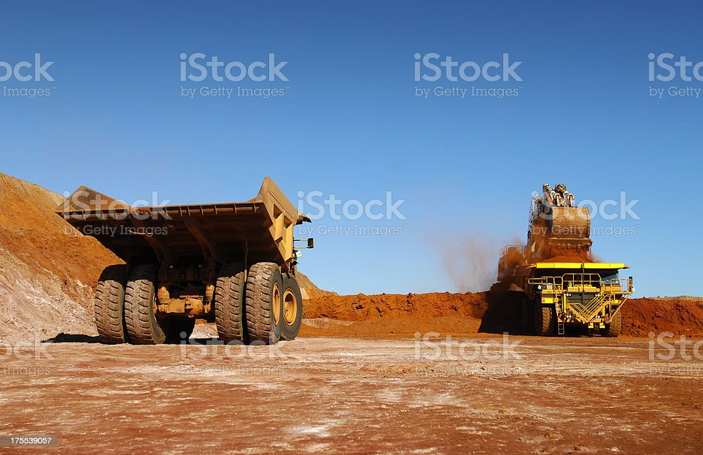 Two haul trucks being loaded with ore. stock photo