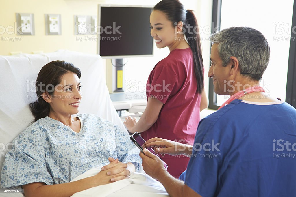 Two health workers next to a woman in a hospital bed stock photo