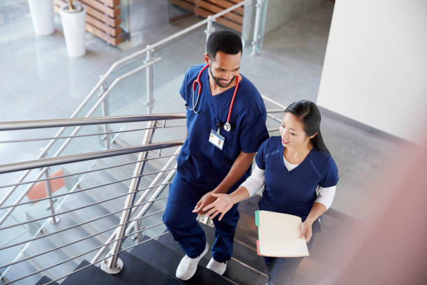 Two healthcare colleagues talking on the stairs at hospital stock photo
