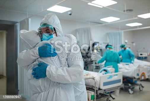 Two healthcare workers hug and support each other.
