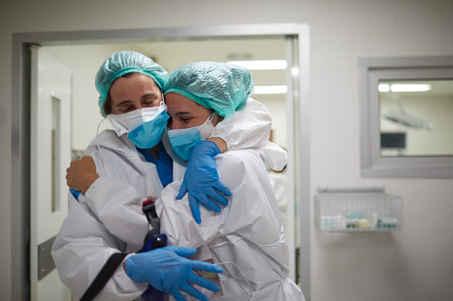 Two doctors hug in celebration of a successful surgery procedure