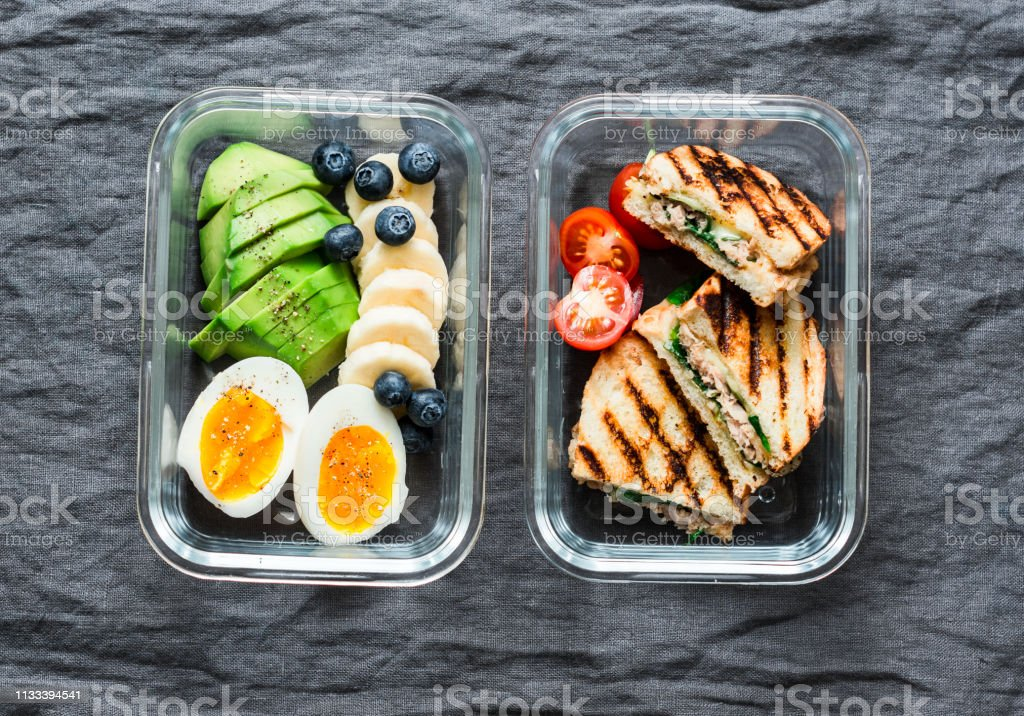 Two healthy office lunch box with sweet and savoury food. Boiled egg,...