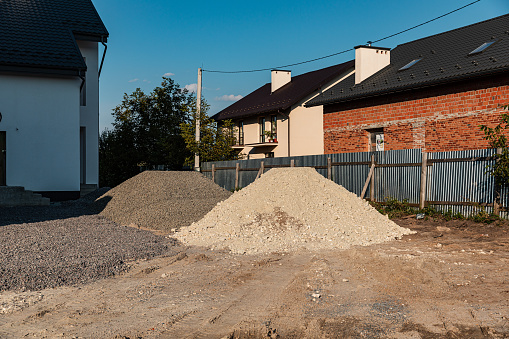 Two heaps of white sand with stones and gray rubble on construction site. Backfill Material. Building foundation concept.