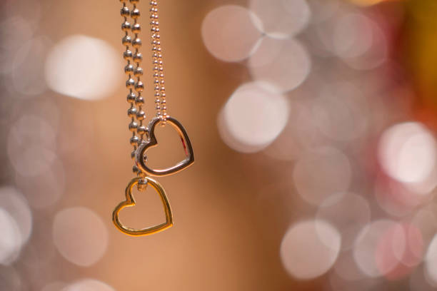 two heart pendants with necklace isolated on soft glowing background stock photo