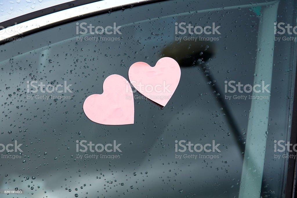 Dos en forma de corazón post-it en una ventana de coche con raindrops - foto de stock