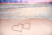 Sand writing of two linked hearts at sunrise