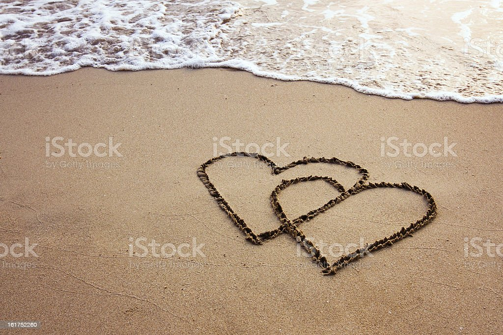 Two hearts drawn in sand on a beach stock photo