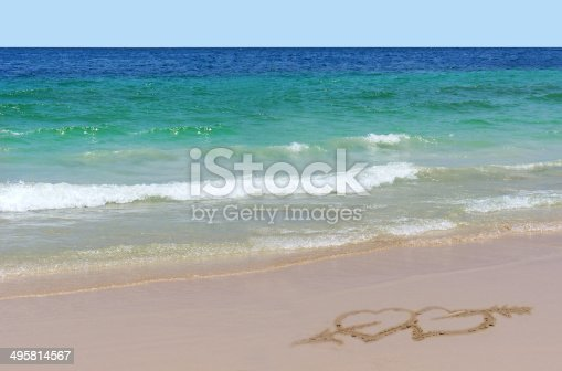 istock Two hearts drawn on sand on beach. Love concept 495814567