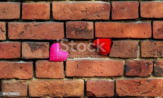 istock two hearts in red and pink hanging on a crumbling old textured brick wall 904289602