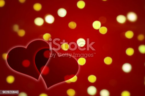 istock Two hearts on a red defocused lights background 902620840