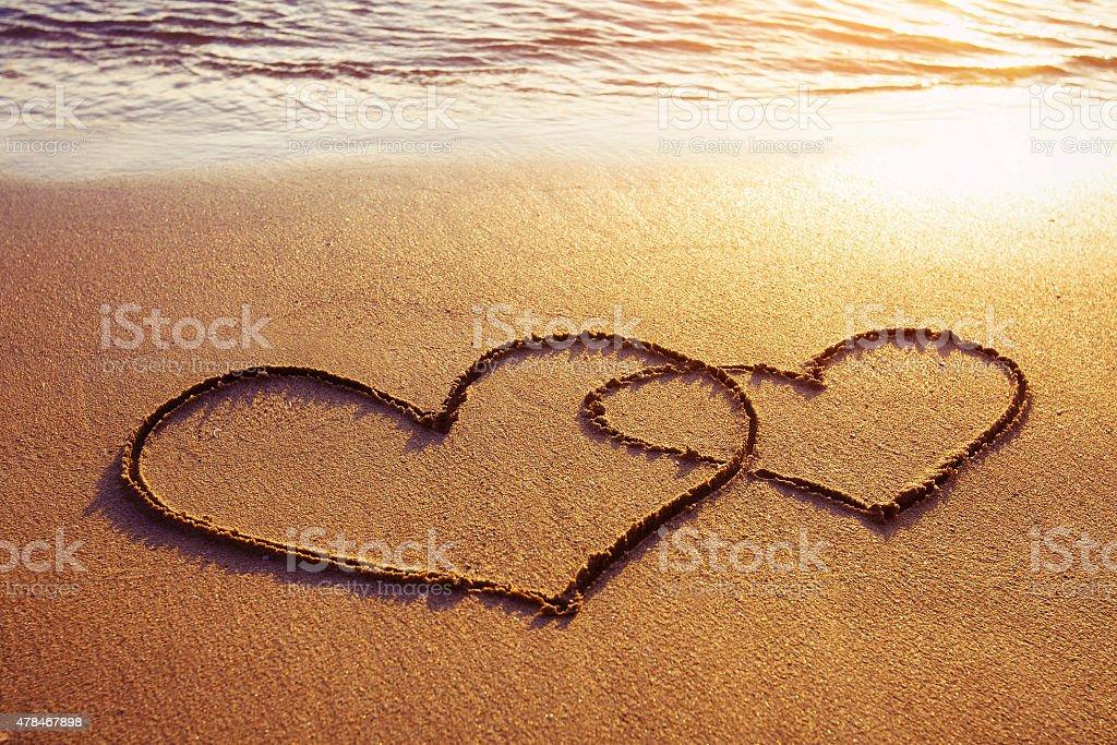 two hearts on sunset beach stock photo
