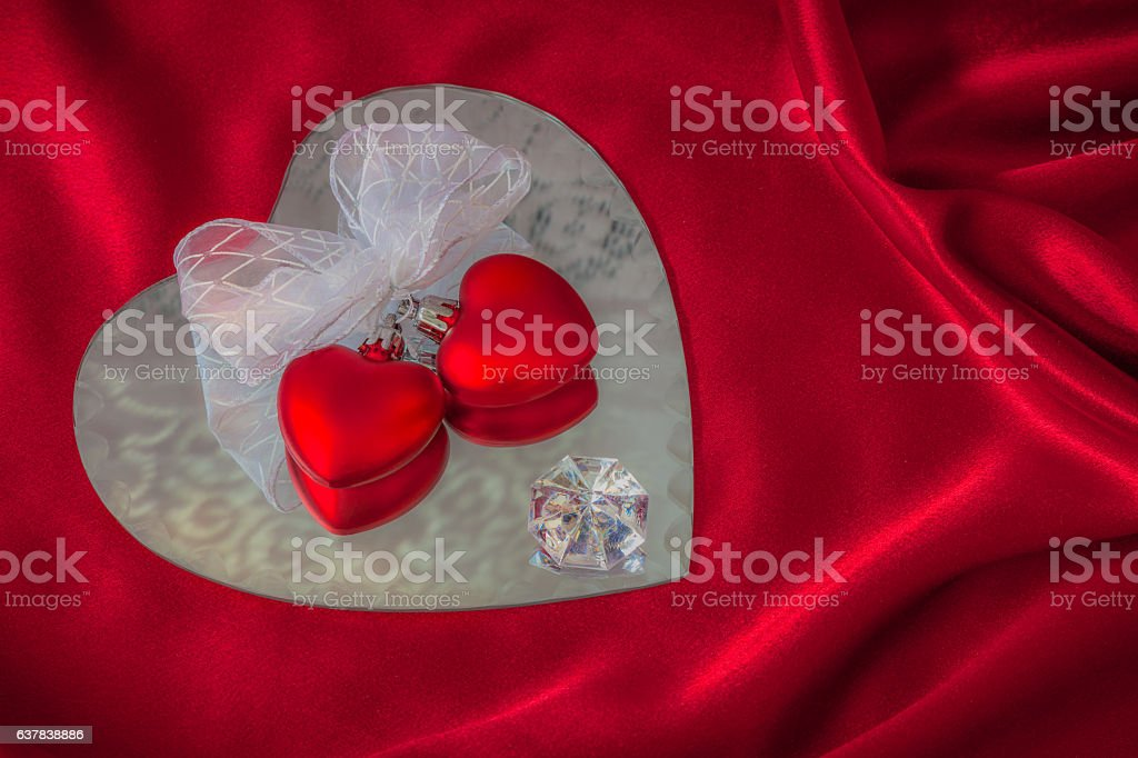 Two hearts ribbon tied with diamond sit on mirror (P) stock photo