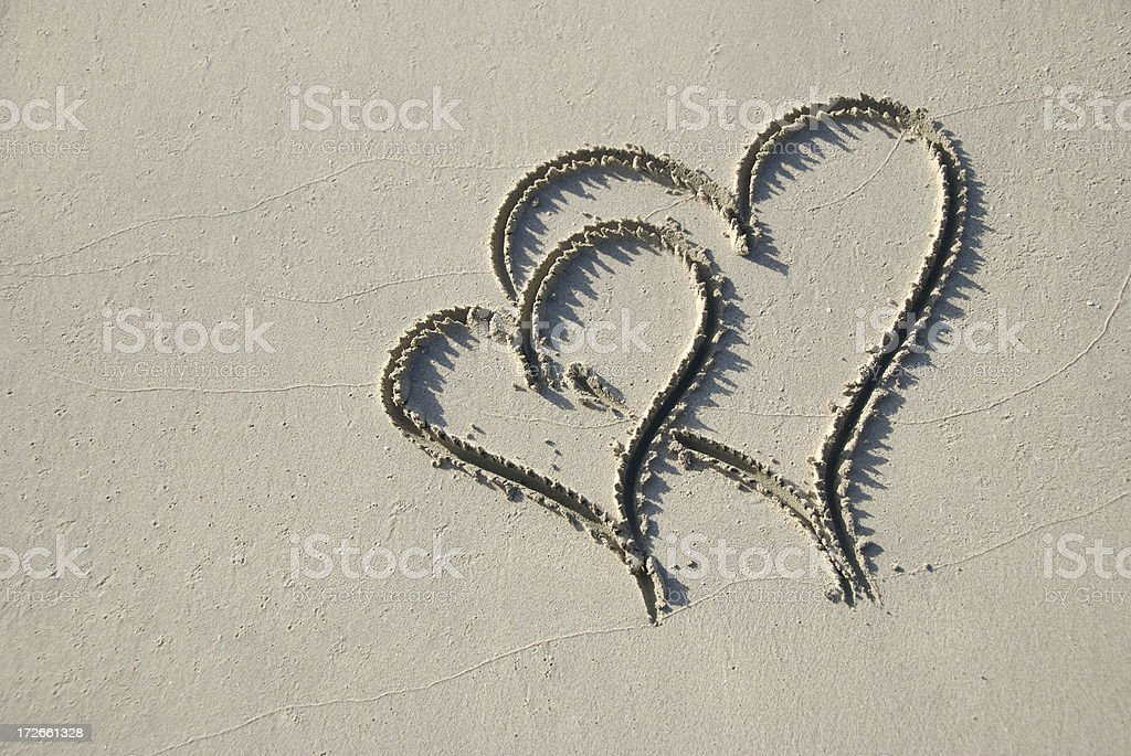 Two Hearts Snuggle in the Sand royalty-free stock photo