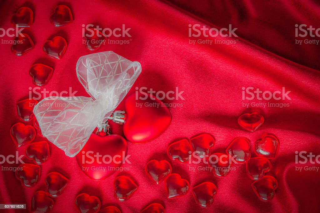 Two hearts tied together with ribbon on red satin (P) stock photo