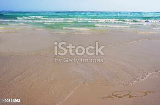 istock Two hearts with an arrow drawn on sand on beach 495814563
