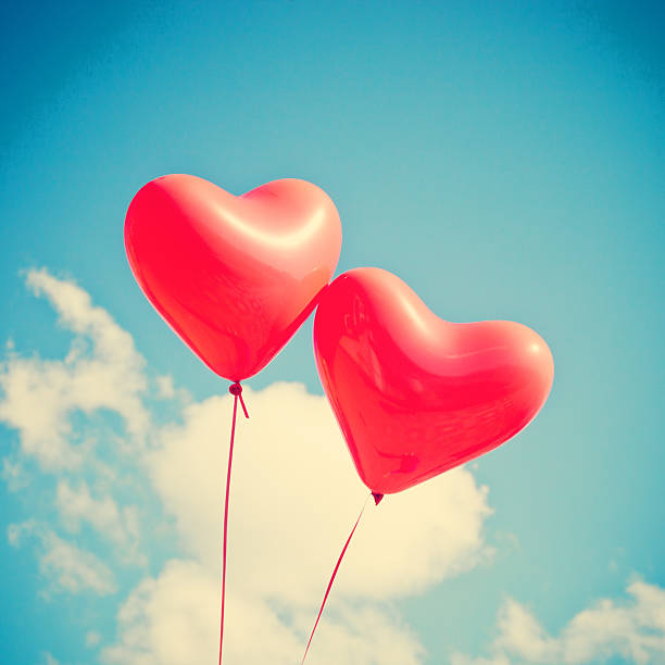Two heart-shaped balloons in the sky stock photo