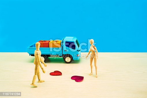 Wooden floor, blue background color, 2 hearts, 2 gifts, blue truck, 2 dolls,