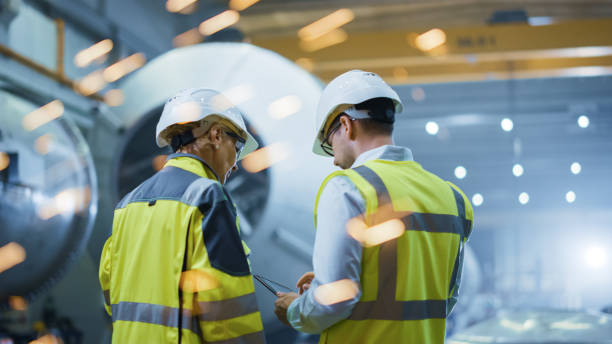 Two Heavy Industry Engineers Stand in Pipe Manufacturing Factory, Use Digital Tablet Computer, Have Discussion. Construction of Oil, Gas and Fuels Transport Pipeline. Back View Sparks Flying stock photo