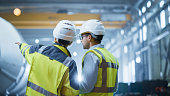 istock Two Heavy Industry Engineers Stand in Pipe Manufacturing Factory, Use Digital Tablet Computer, Have Discussion. Construction of Oil, Gas and Fuels Transport Pipeline. Back View Sparks Flying 1224034724