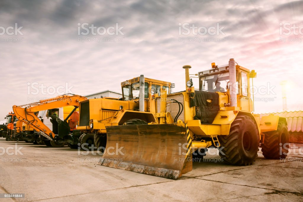 Two heavy wheeled tractor one excavator and other construction machinery in the morning sun стоковое фото