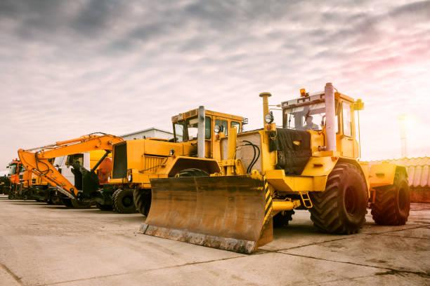 Zwei schwere Rad Traktor ein Bagger und andere Baumaschinen in der Morgensonne – Foto