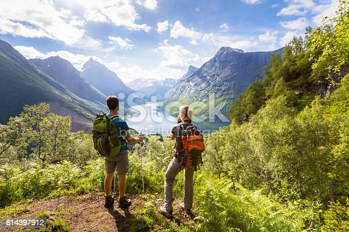Two hikers at viewpoint in the mountains enjoying beautiful view of the valley with a lake and sunny warm weather in summer, green trees around